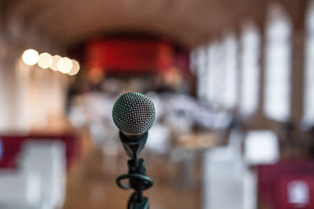 A closeup shot of a microphone in a restaurant with a blurred background