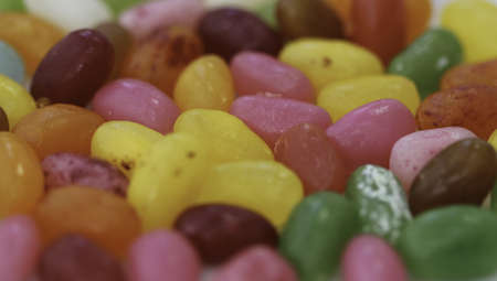 A closeup of colorful jelly beans under the lights with a blurry background Фото со стока
