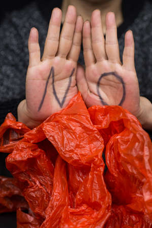 A vertical closeup shot of word 'NO' written on a woman's hand in front of a plastic bag - Saying NO to plastic