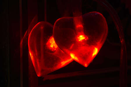 A closeup shot of two red hearts with lights burning inside Stock fotó