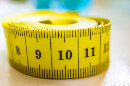 A closeup shot of a yellow tape measure with a blurred background Фото со стока
