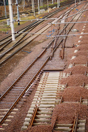 A vertical high angle closeup shot of graded stones on the rails of a train