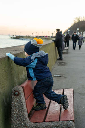 POZNAN, POLAND - Jan 05, 2020: Young boy with warm clothes standing on a wooden bench by a barrier at the seaside on a cold winter day.