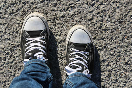 A high angle shot of a person's feet standing on the asphalt Stock fotó