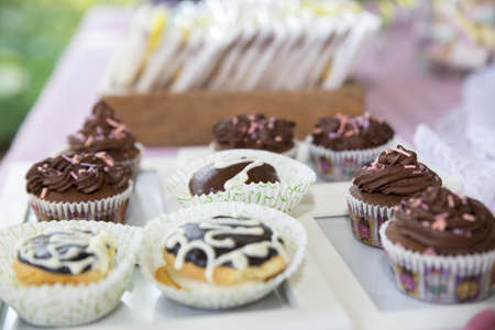 A closeup of chocolate cupcakes on the table under the lights with a blurred background