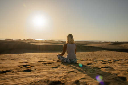 A person calmly meditating in the dunes of Maspalomas at sunrise, for recreation