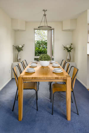 A vertical shot of a wooden table with chairs in the dining room with white walls