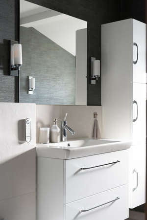 A vertical shot of a bathroom with a mirror and white furniture Imagens