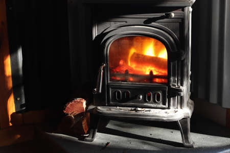 An old metal fireplace with logs of wood and fire burning inside it Stock fotó