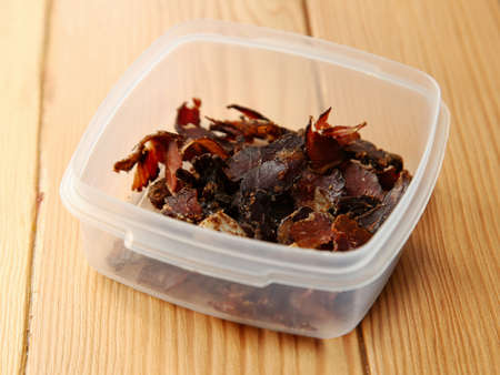 A plastic container filled with biltong snacks on a wooden surface