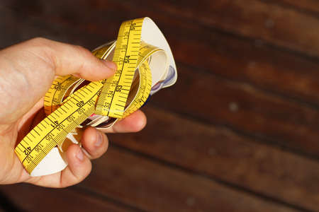 A closeup shot of a person holding a measuring tape over a wooden surface
