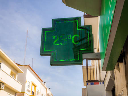 A low angle shot of the sign of pharmacy with a thermometer displaying 23 degrees Celsius
