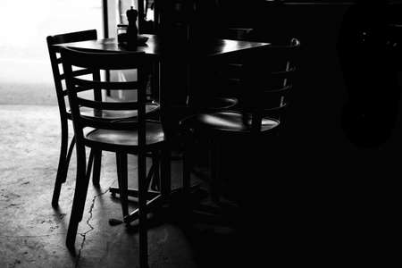 A greyscale shot of a table with chairs in a dark room during daytime