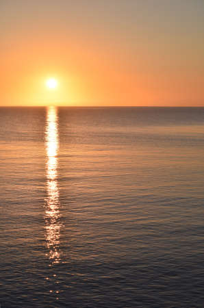 A vertical picture of the sea with the sun reflecting on the water during a golden sunset 版權商用圖片