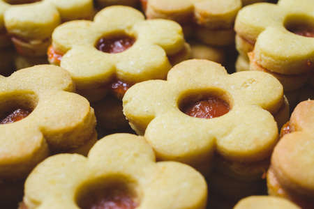 A closeup shot of flower-shaped cookies with jam