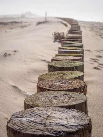 A vertical high angle shot of a long line of wooden docks on the sandy ground 版權商用圖片 - 155890355