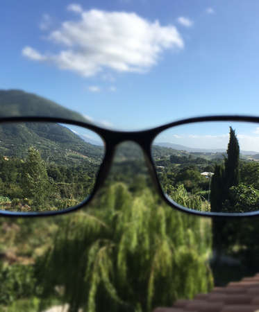 A vertical shot of a clear image of green trees, green mountain seen in the eyeglasses with a blurred background