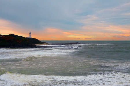 The foamy ocean under the colorful sky and a small lighthouse in the background Stock fotó
