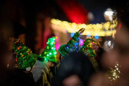 A colorful street festival with people in Christmas tree hats and bokeh lights in the background