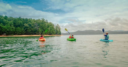 A family riding a kayak on a sea surrounded by hills covered in greenery under a cloudy sky 版權商用圖片