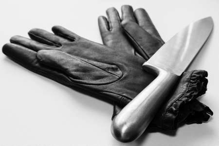A selective focus shot of metal knife over black gloves on a white surface