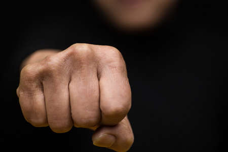 A closeup shot of a Chinese female holding her fist as a sign of strength-women empowerment concept