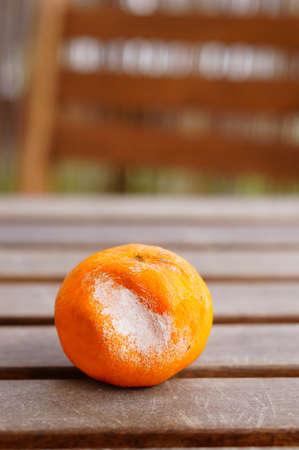 A vertical closeup shot of a rotten tangerine on a wooden surface Foto de archivo