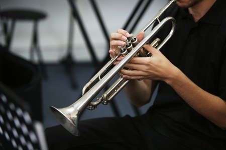 A selective focus shot of a person playing the trumpet
