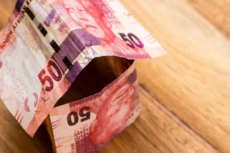 A high angle shot of some South African rand bills on a wooden surface Stock Photo