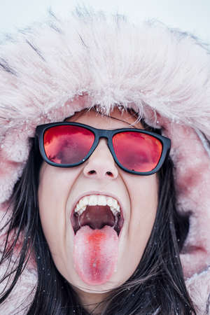 A closeup shot of a happy woman wearing a hoodie showing her tongue with a reddish streak