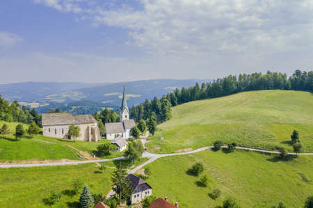 An amazing shot of the Lese church in Slovenia in a valley with a cloudy sky