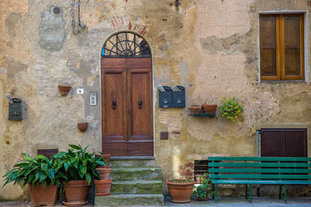 A beautiful shot of an old building with a wooden door and a bench in front
