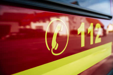 German red Firetruck with emergency alarm dial number