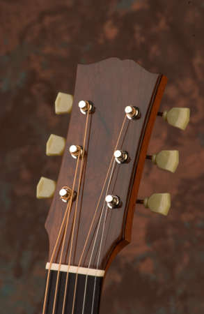 A vertical picture of a brown acoustic guitar headstock under the lights against a blurry background Stock Photo