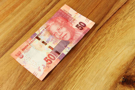 A high angle shot of a South African 50 rand bill on a wooden surface