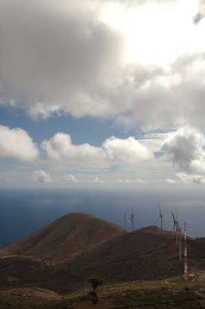 The sea surrounded by hills covered in plants and windmills under sunlight and a cloudy sky