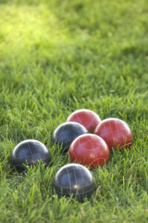 A vertical picture of colourful bocce balls on the lawn under the sunlight with a blurred background Stock Photo