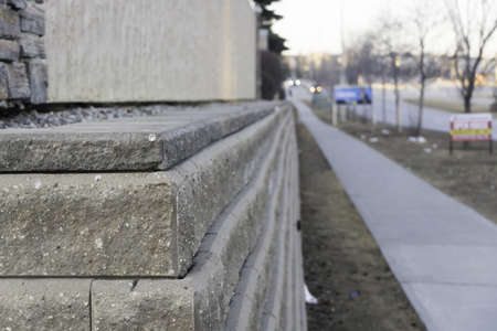 A building's wall with a blurred sidewalk in the background