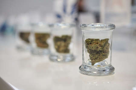 A closeup shot of a cannabis flower in a small glass jar on a white surface