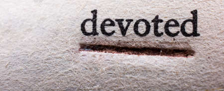 The word devoted typed and underlined on a surface