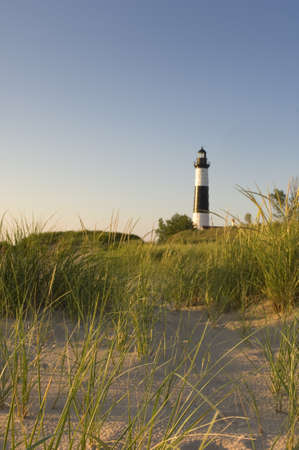 The Big Sable Point Lighthouse surrounded by greenery and sand under the sunlight in Michigan