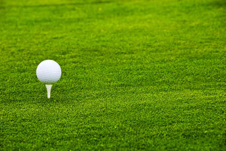 A landscape shot of a white golf ball in a greenfield