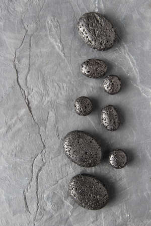 A vertical greyscale shot of lava beads on a wooden surface