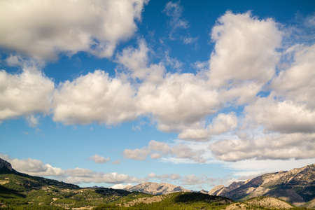 A beautiful shot of a blue sky full of clouds above mountains covered in trees in Polop, Spain