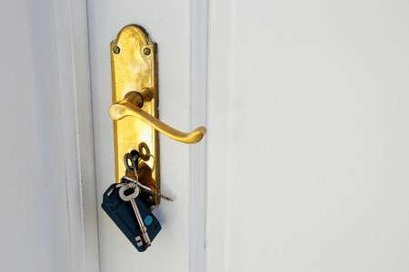 A golden doorknob with keys on a white door