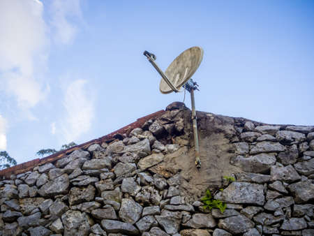 A low angle shot of a dirty weathered antenna on the rooftop during daytime