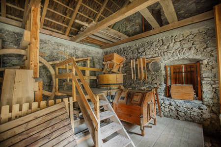 A stunning shot of an old mill made out of wood in an old stone building with a wooden roof