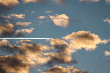The trail of an airplane in the sky with dark clouds