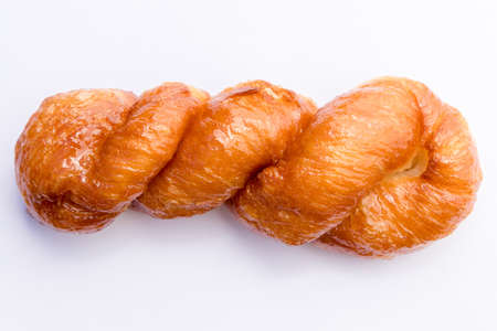 A closeup shot of a traditional South African koeksister donut on a white paper Imagens