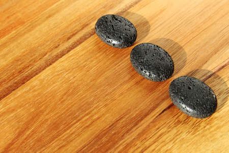 A wooden surface with black lava beads in a spa salon - great for background or wallpaper